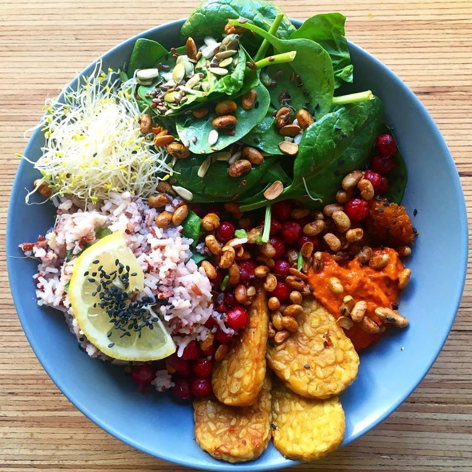 Healthy and colourful food bowl at Mana Berlin, filled with green spinach leaves, white and brown rice, carrots, tempeh, nuts, seeds and a slice of lemon on top.