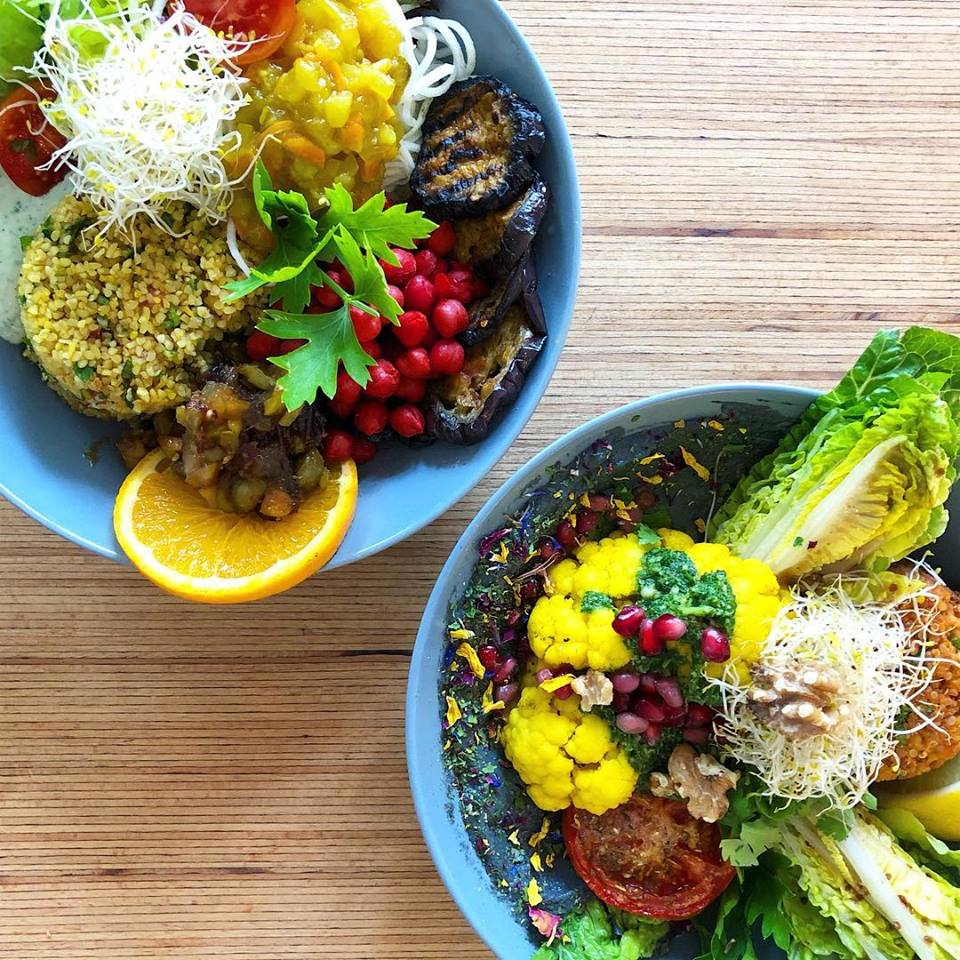 Healthy food bowls at Mana Berlin, one filled with tabouleh, aubergine, mango chutney and the second one with cauliflower, salad, tabouleh, topped with pomegranate seeds.