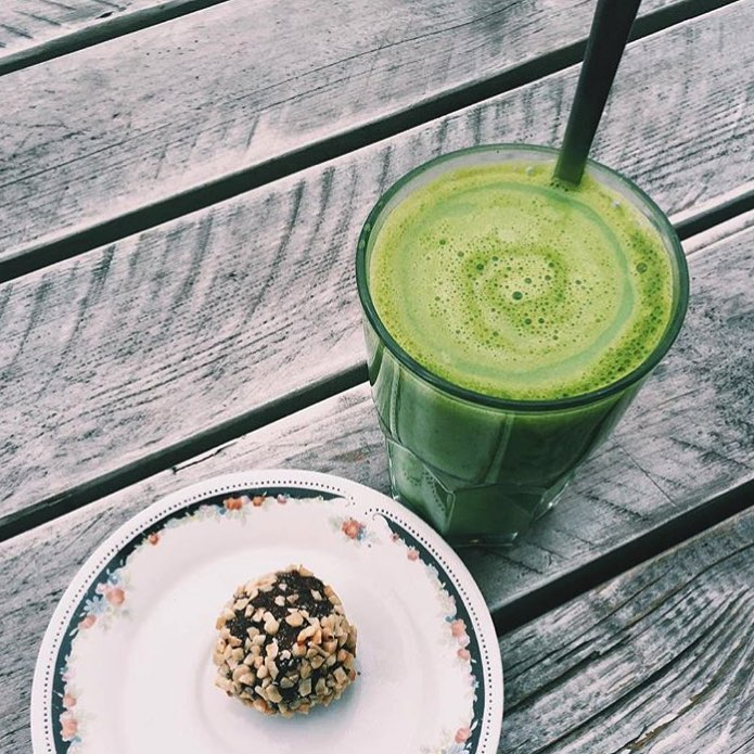 Green smothie and energy ball covered with nuts on a wooden table at Goodies Berlin