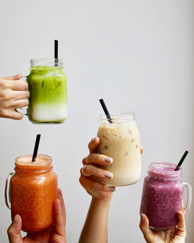 Four different hands holding up smoothies in different colours at Goodies Berlin