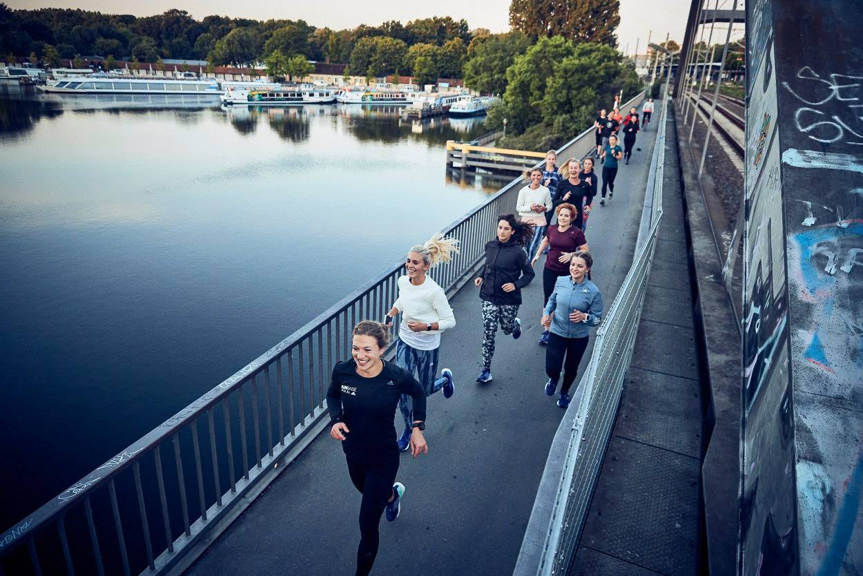 A group of Adidas runbase runners on their jog over a bridge in Berlin, crossing the Spree.