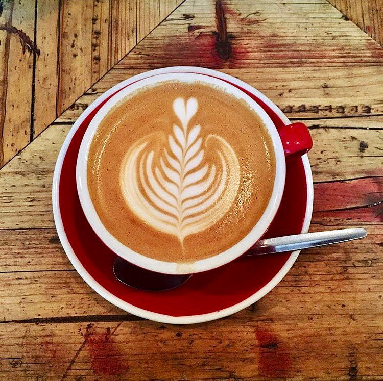 Flat White coffee with leaf milk art in a red cup on a wooden table