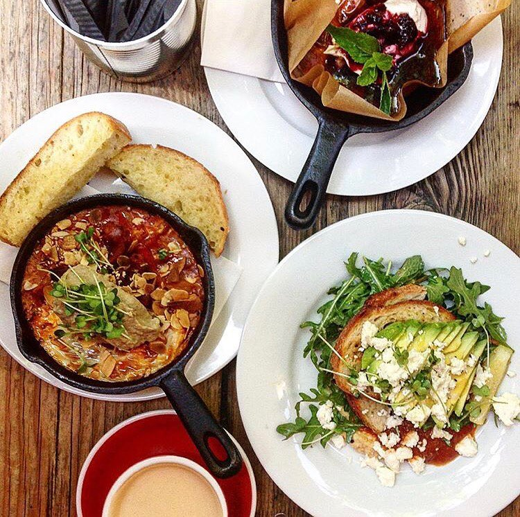 Baked eggs in a tomato sauce bubbling in a pan with Sironi bread on the side, avocado on Sironi bread and baked pancakes with beries and mascarpone in a small black pan at Silo Coffee Berlin