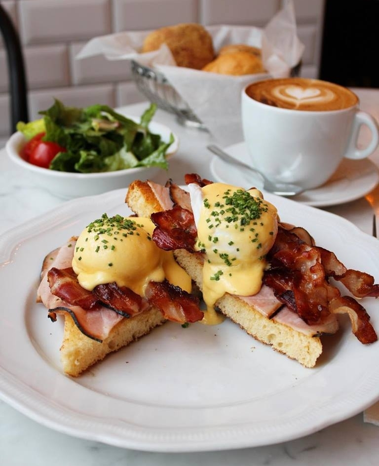 Eggs benedict with sauce hollandaise and bacon on toasted bread at Benedict Berlin