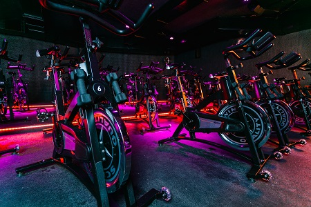Black spin bicycles with weights in front in a dark room with pink lights at ride berlin
