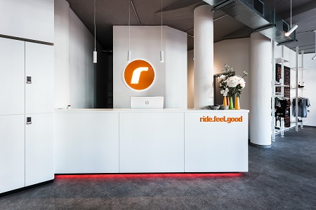White desk with orange ride berlin logo and ride feel good sign at the entrance of ride berlin west studio.