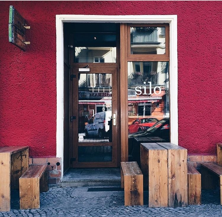 Wooden tables in front of glass entrance door to Silo coffee Berlin