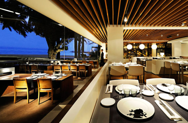 Interior view of Bestial restaurant in Barcelona and its terrace with sea view in the background