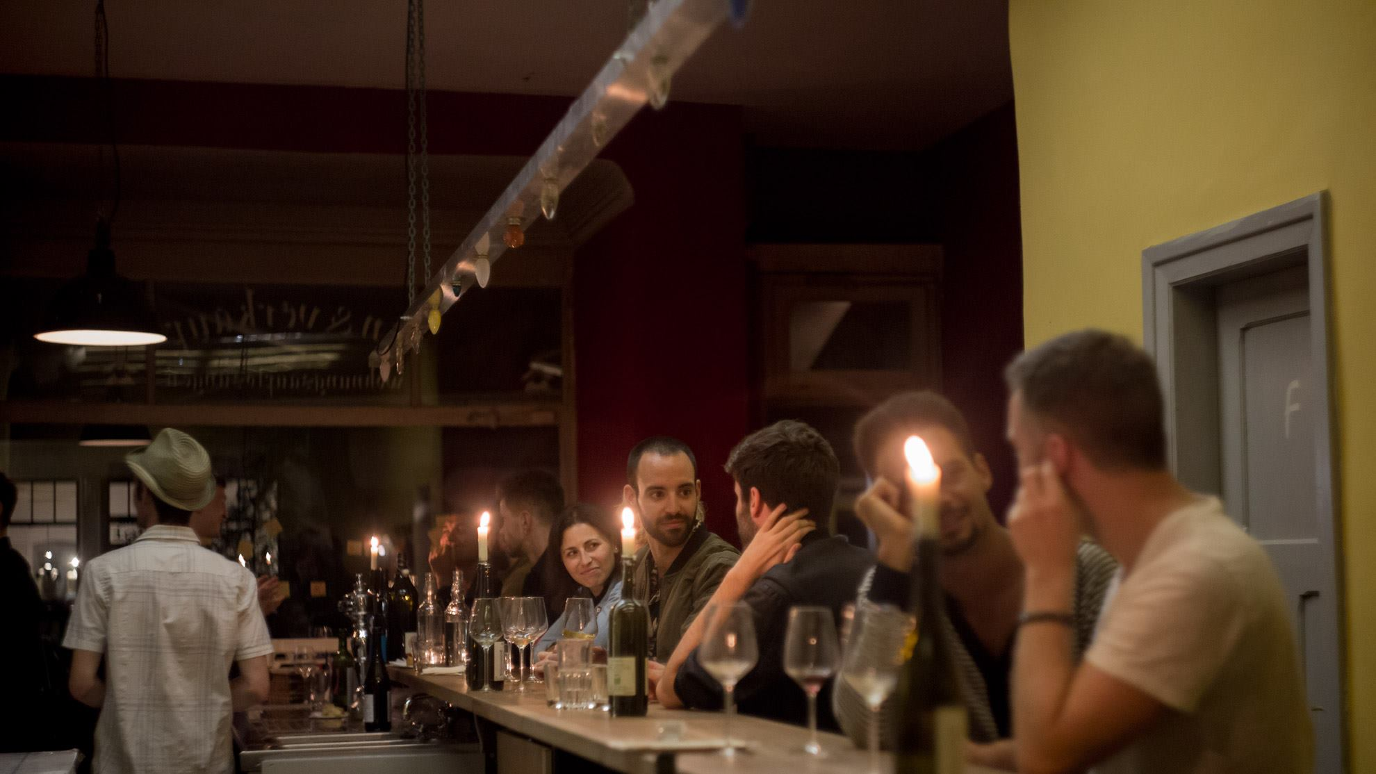 A crowd sitting at bar with wine glasses, bottles and candles at Naturales Weinbar Berlin