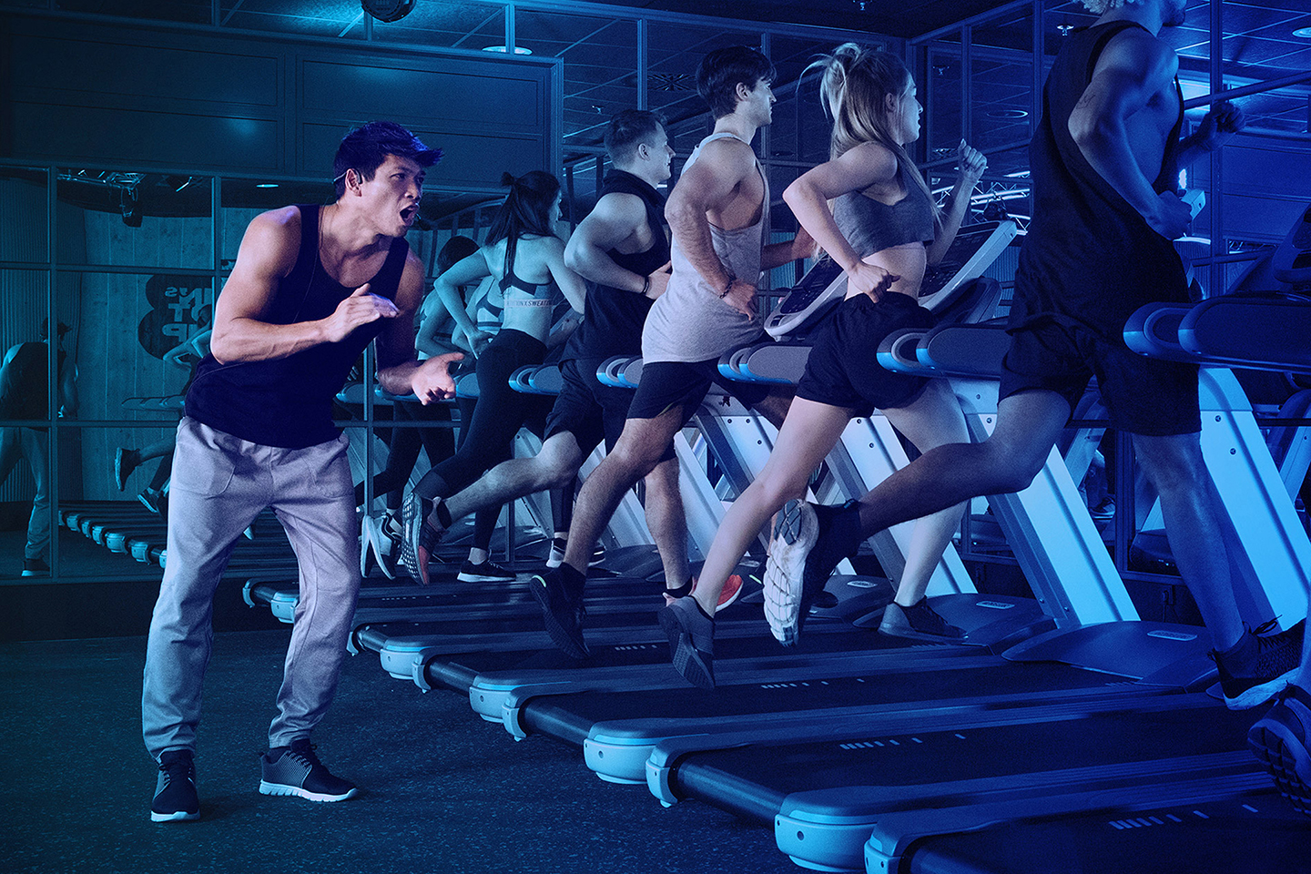 Girls and guys on treadmills running in a dark room with a trainer standing behind them cheering at John's Bootcamp Berlin Powerbase