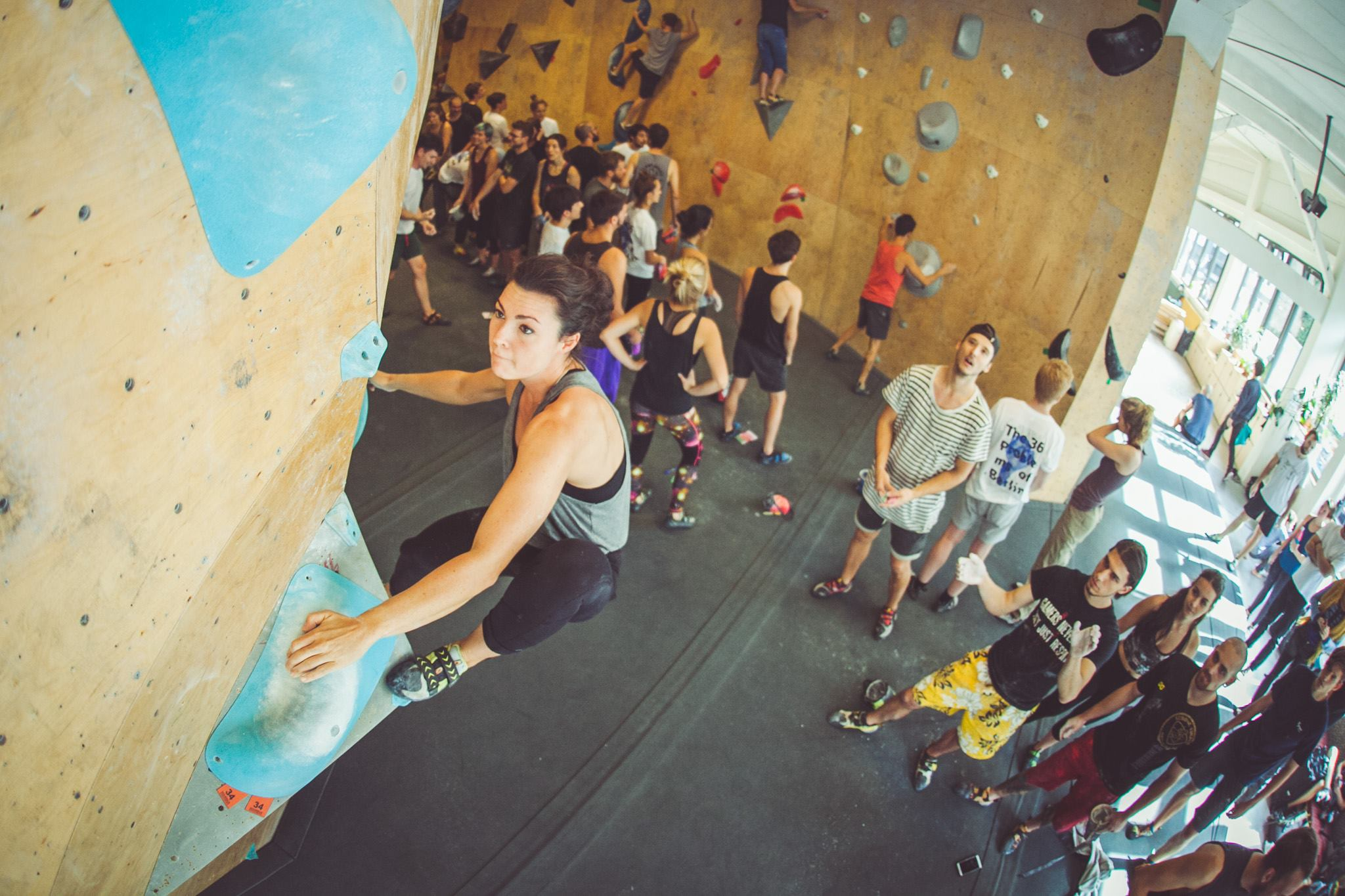 Girl climbing up a wall at Berlin Boulderklub while other people are watching