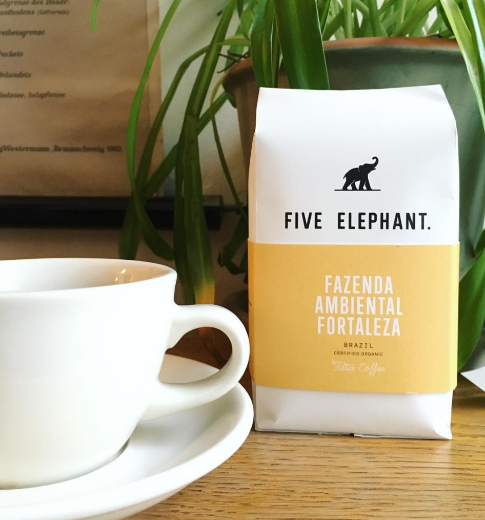 Brazilian coffee in a white packaging by Five Elephant Berlin on a wooden table and a white cup of coffee next to it