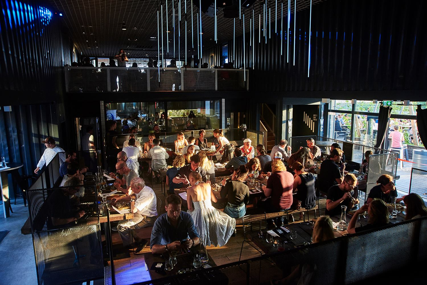 People sitting at wooden tables at BRLO BRWHOUSE Berlin location with a second floor and garden, enjoying food and craft beer
