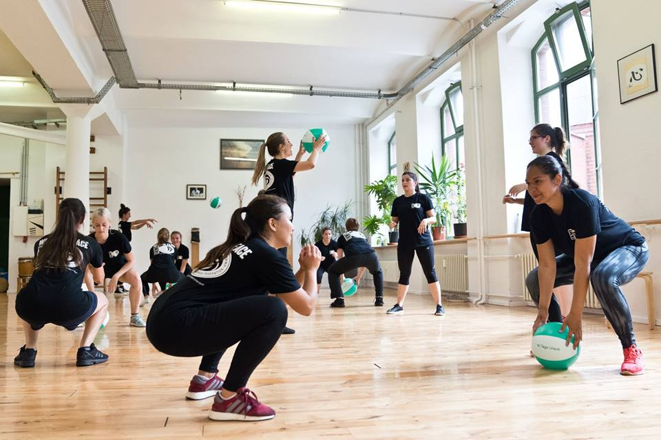 Girls working out with medicine balls as part of Krav Maga training at Walk in Peace Berlin