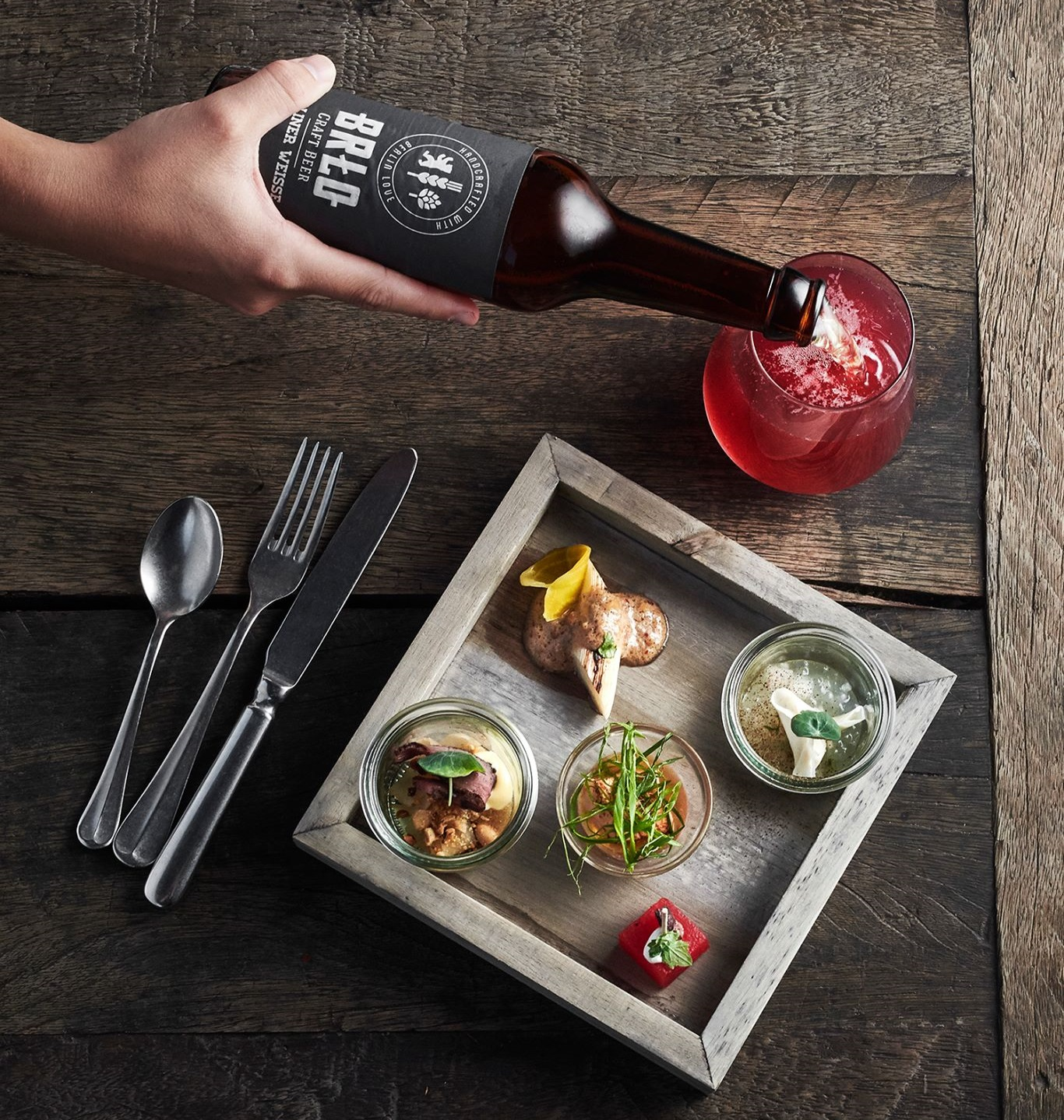 BRLO Tastingboard with delicious dishes and a glass of BRLO Berliner Weisse beer poured from a bottle