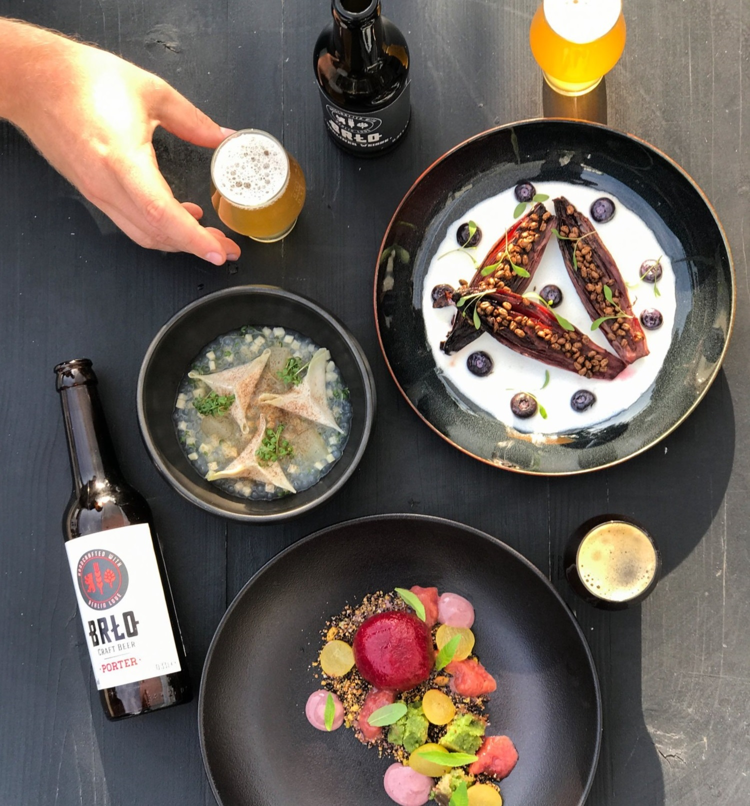 Three different dishes arranged on black stylish plates, BRLO craft beer next to them, a Porter and a pale ale