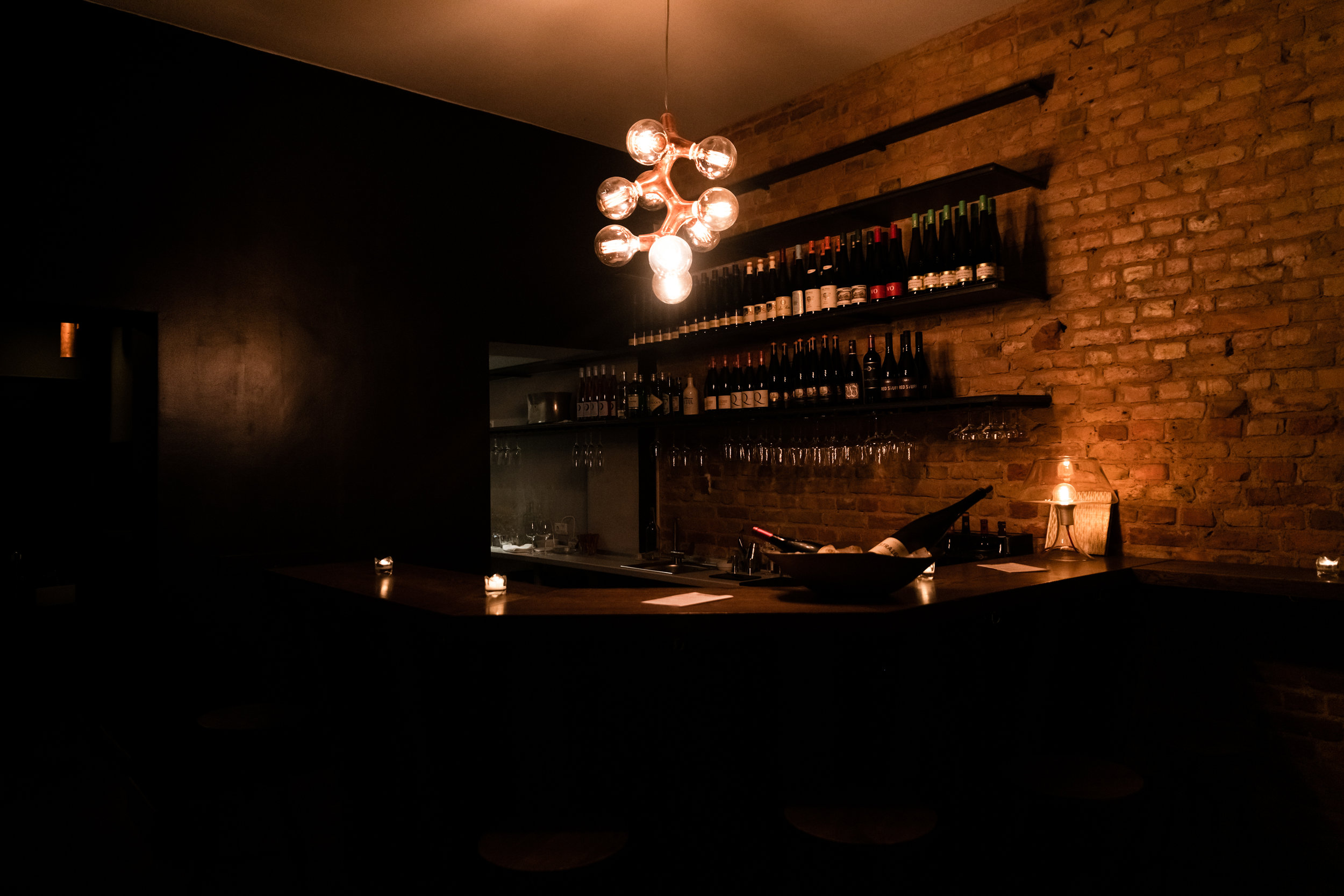Gloomy view of exposed brick wall and shelves with wine bottles at Freunde bar