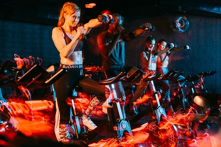 Girl on spinning bike in Björn Borg pants and weights in hand