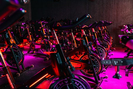 Spin bikes in a ride berlin room lightened up in pink