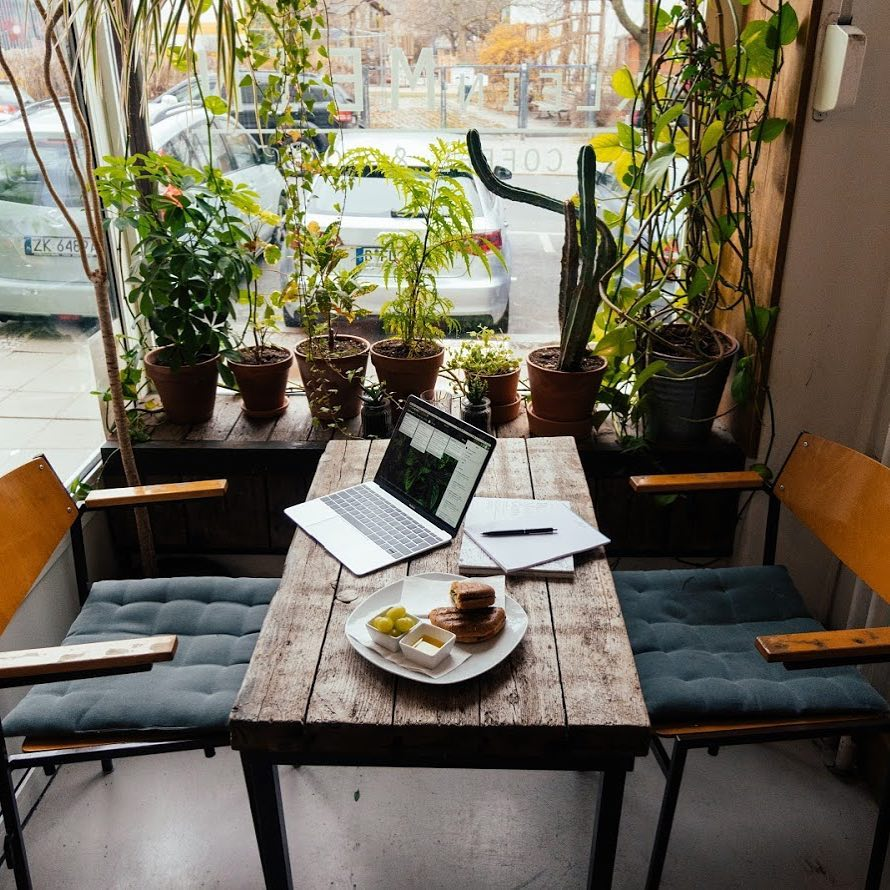 Laptop and food on a wooden table at KleinMein Coffee