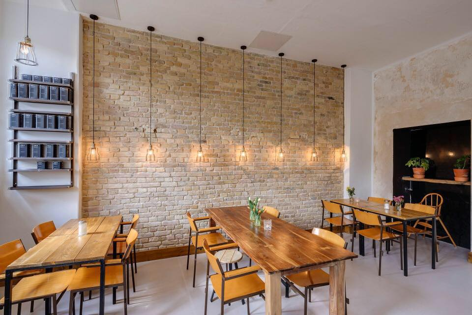 Brick wall with hanging lamps and wooden table, KleinMein Coffee interior view
