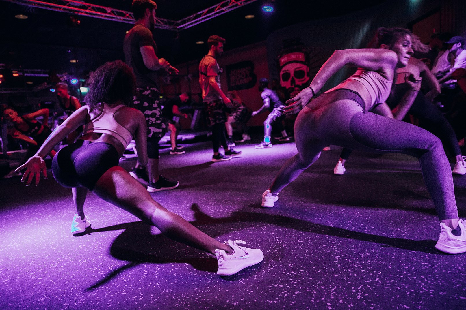 Girls and guys in workout gear, doing side lunges in a dark room with purple lights at John&Janes Powerbase Bootcamp Berlin