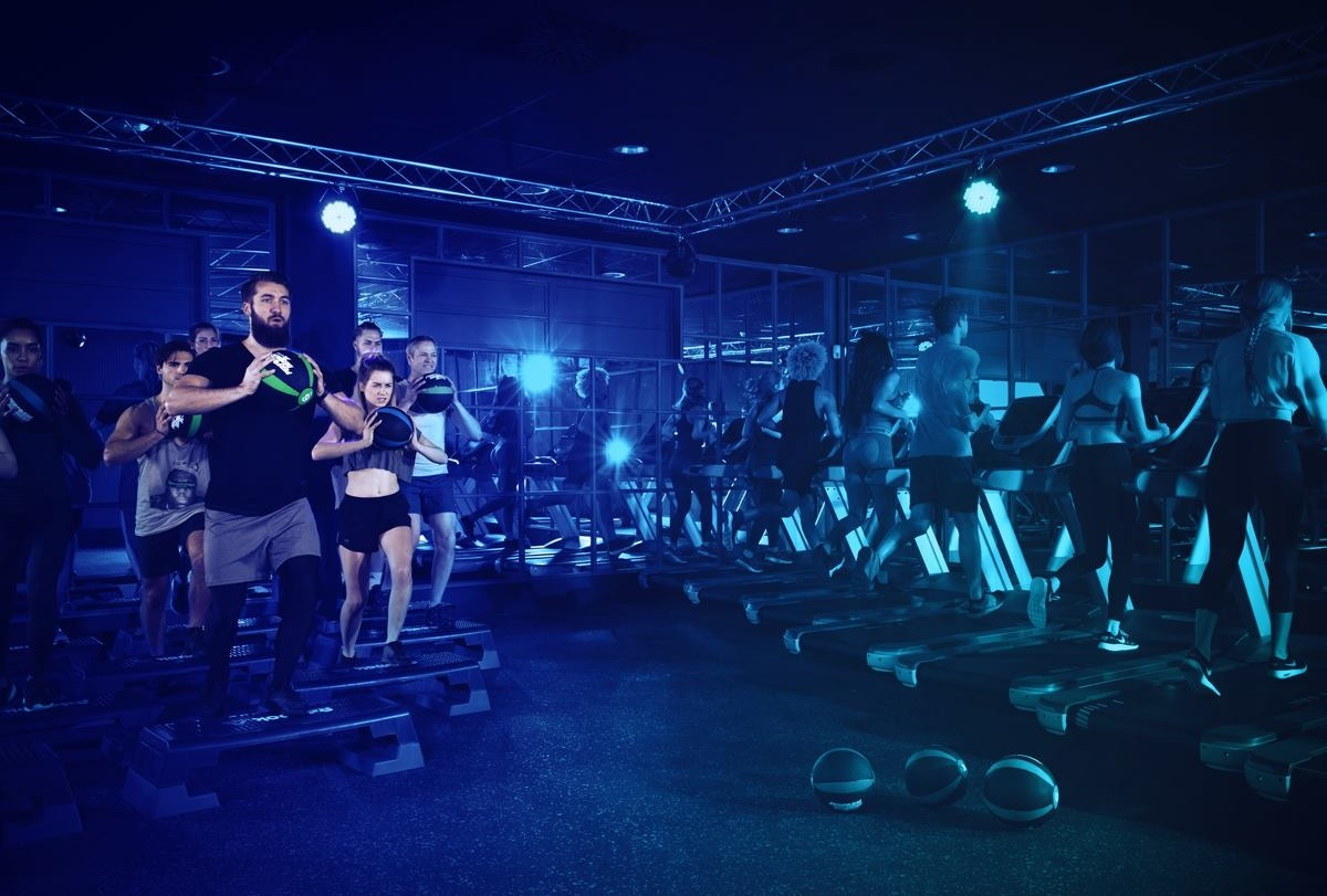 A group of people on treadmills while another group is working out on a step with medicine balls in hand in a dark room with blue lights at John's bootcamp Berlin