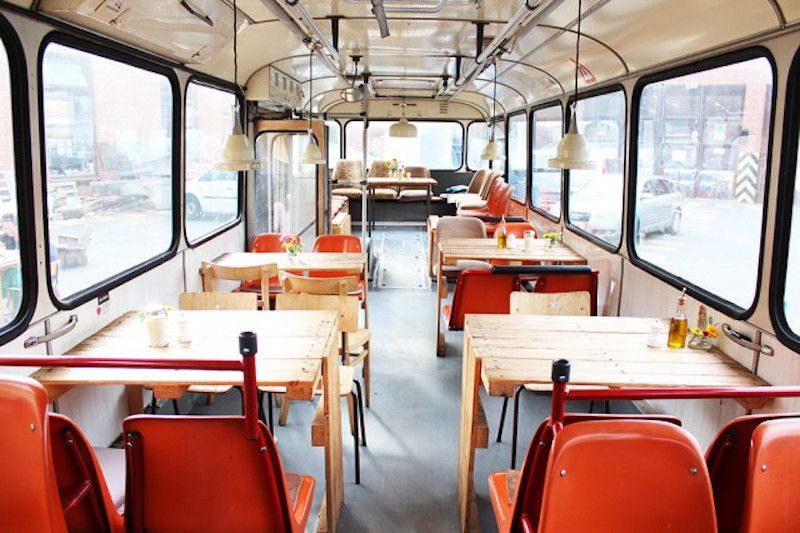 Red plastic chairs and wooden tables inside a BVG bus at Cafe Pförtner