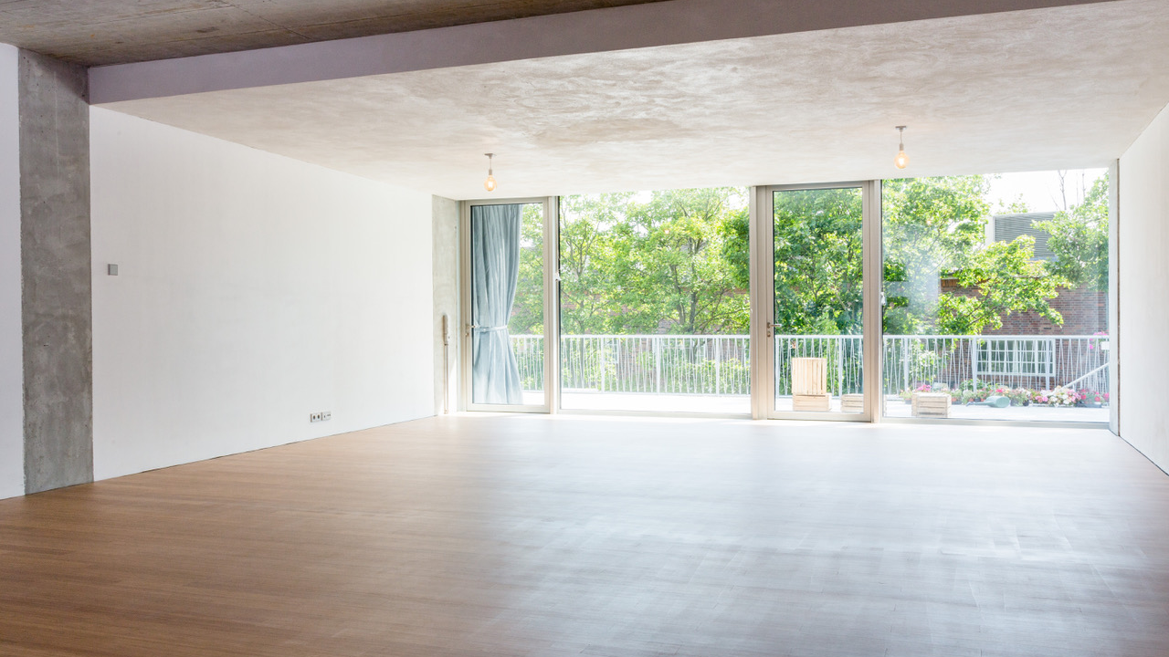 Large and sunny yoga class room with wooden floor and windows looking out on a balcony