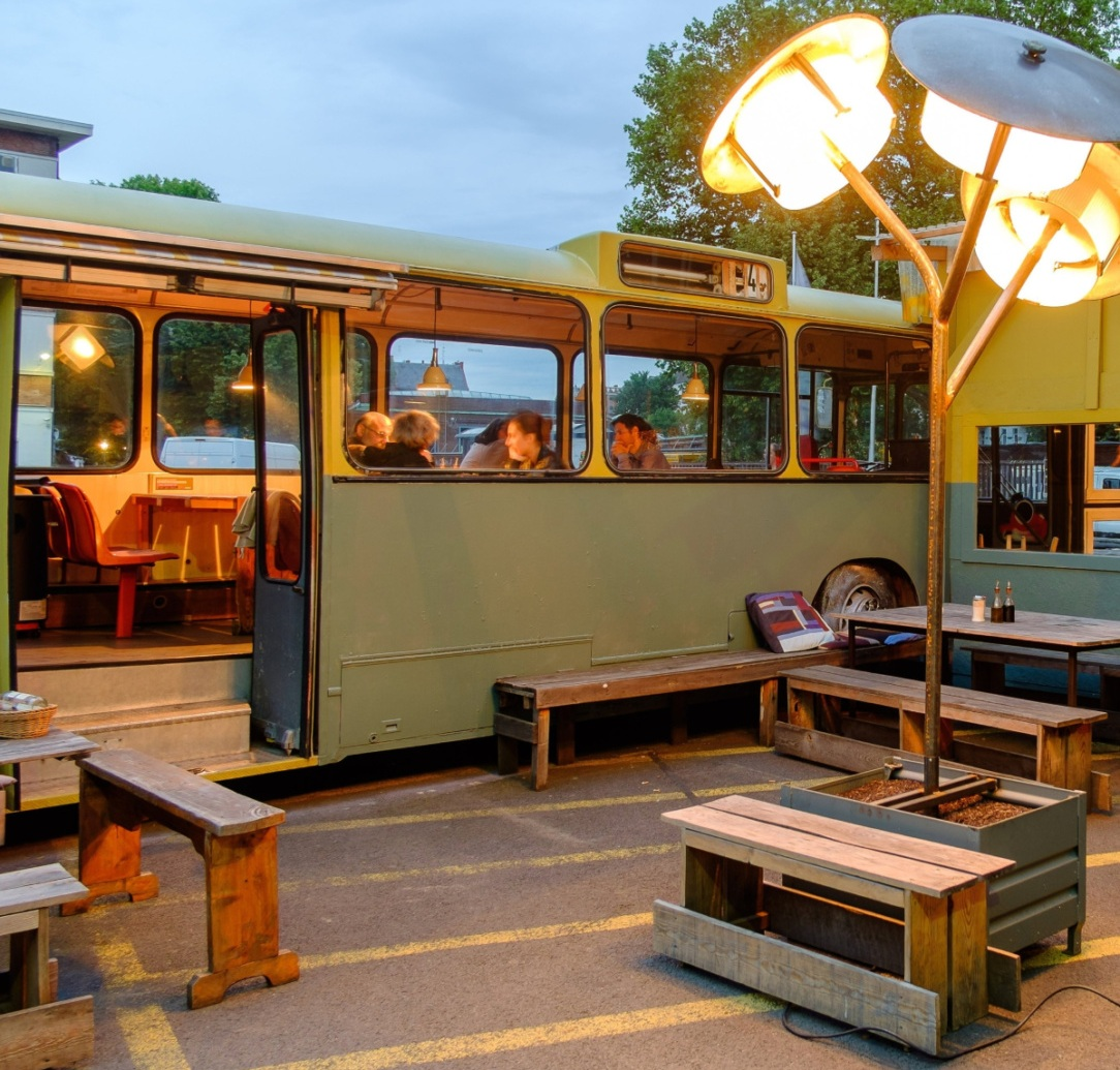 People dining in an old BVG bus at Cafe Pförtner with wooden chairs and tables in front of the bus.