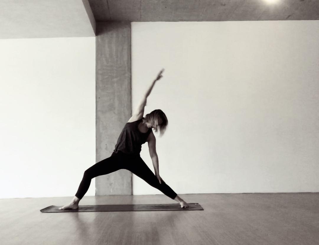 Yoga teacher Nicola Tröger on a mat in Warrior 4 pose, Virabhadrasana.