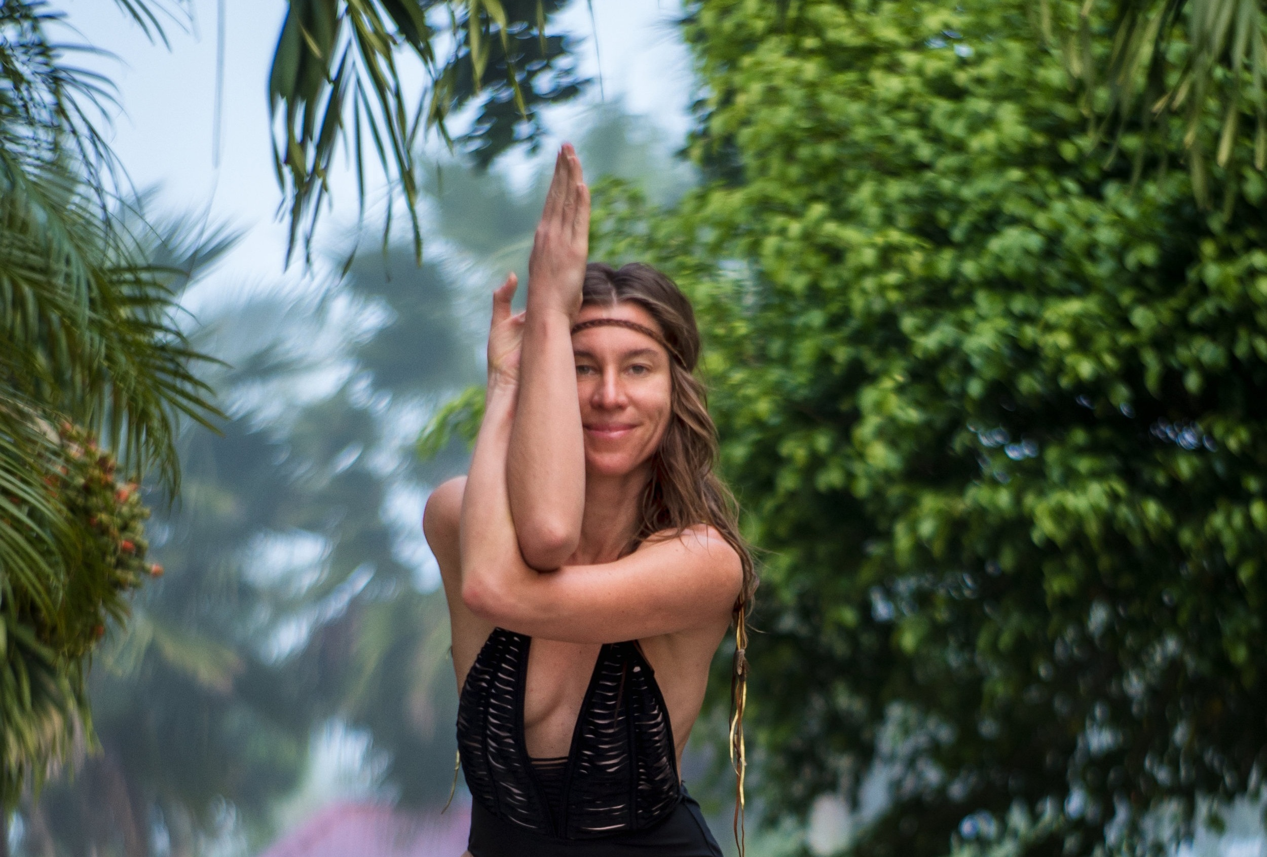 Yoga teacher Eva Kaczor in a body suit with her arms intertwined in a yoga pose with trees in the background
