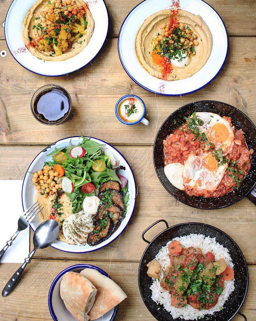 Israeli street food dishes served at Gordon, Sabich, hummus, pita bread, aubergines, eggs, tomatoes in a pan with herbs
