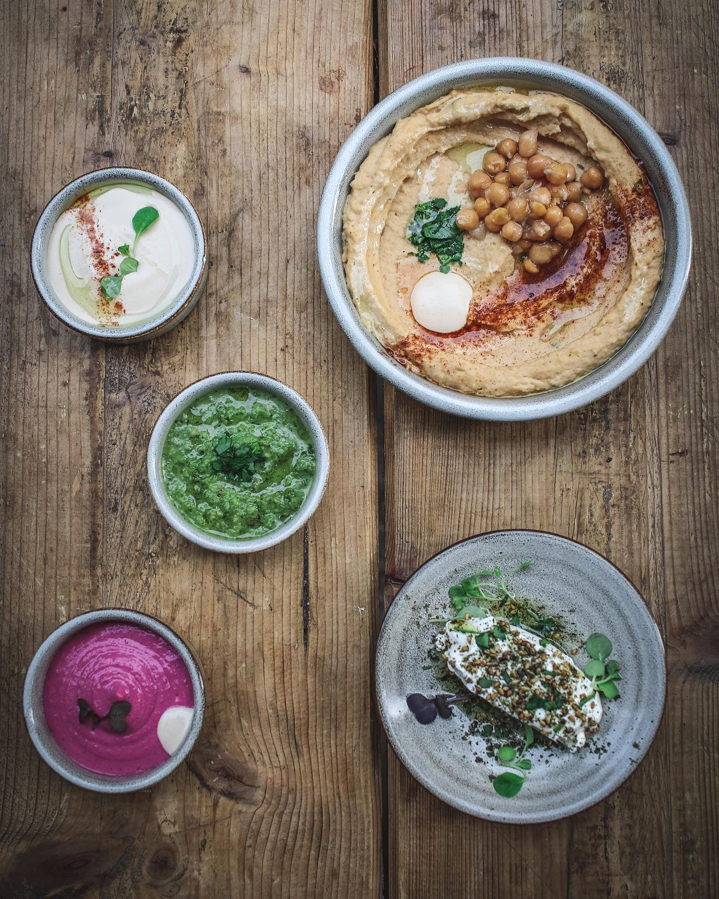Hummus and dips served at Gordon. Zhug hot sauce, labaneh and beetroot dip in bowls on a wooden table