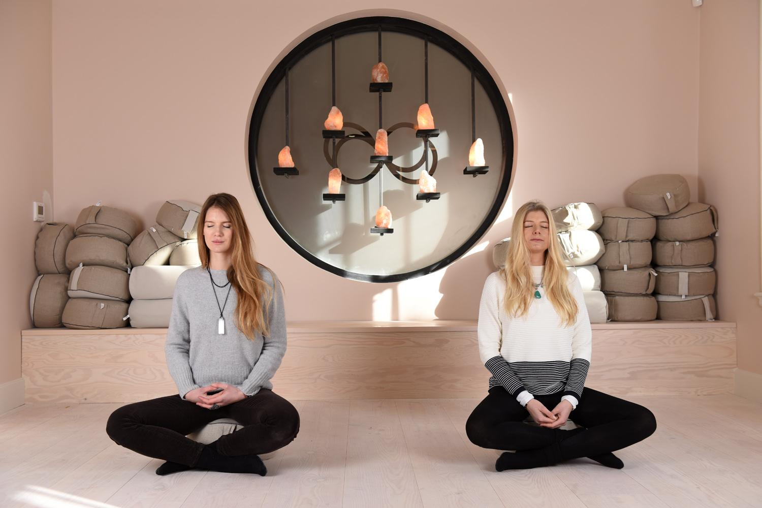 Two ladies in lotus pose on a cushion, meditating at Remind London Victoria.