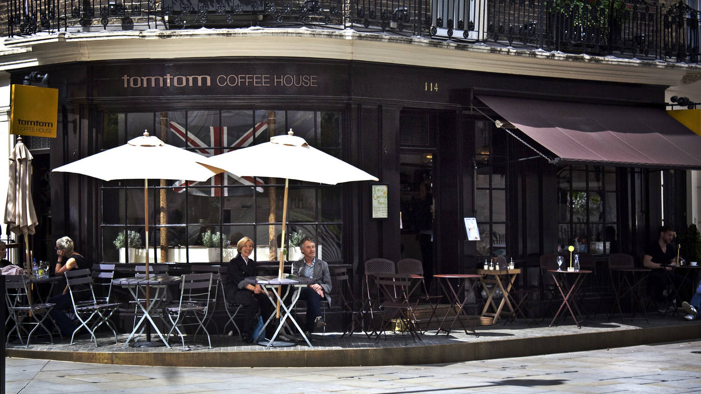 Terrace with cute tables and umbrellas in front of tomtom coffee house in London.