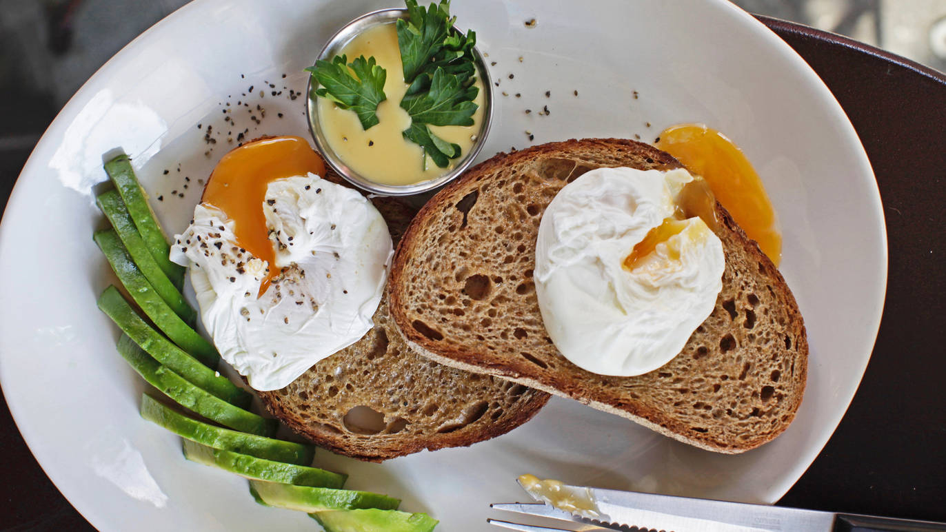 Poached eggs on rye bread with avocado on the side at Tomtom coffee London.