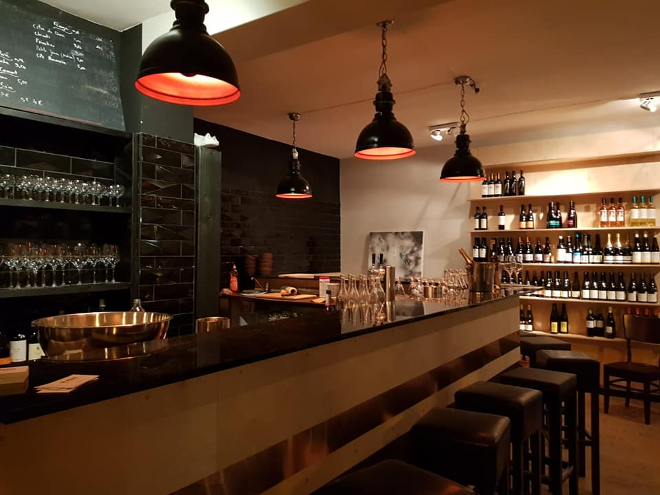 Interior view of Dr. Maury´s cosy bar with wine glasses and wine bottles
