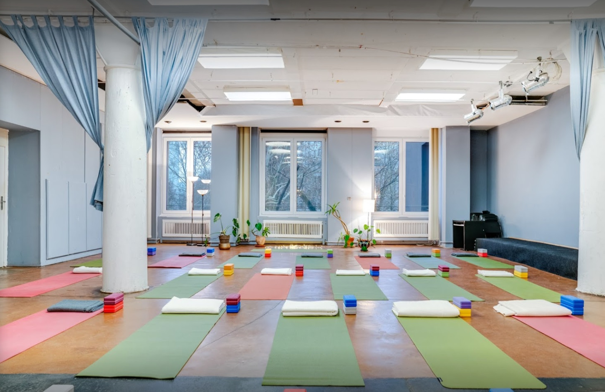 Yoga mats with props and blankets laid out in the spacious and bright HiYoga Berlin room.