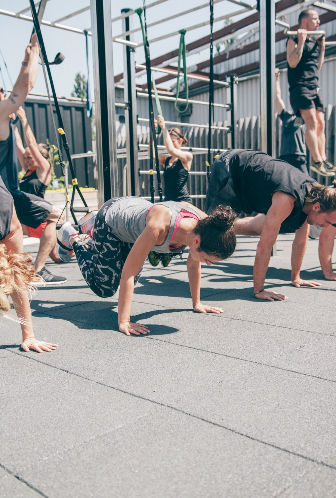 Guys and girls doing different workouts on TRX straps outdoor at adidas runbase Berlin