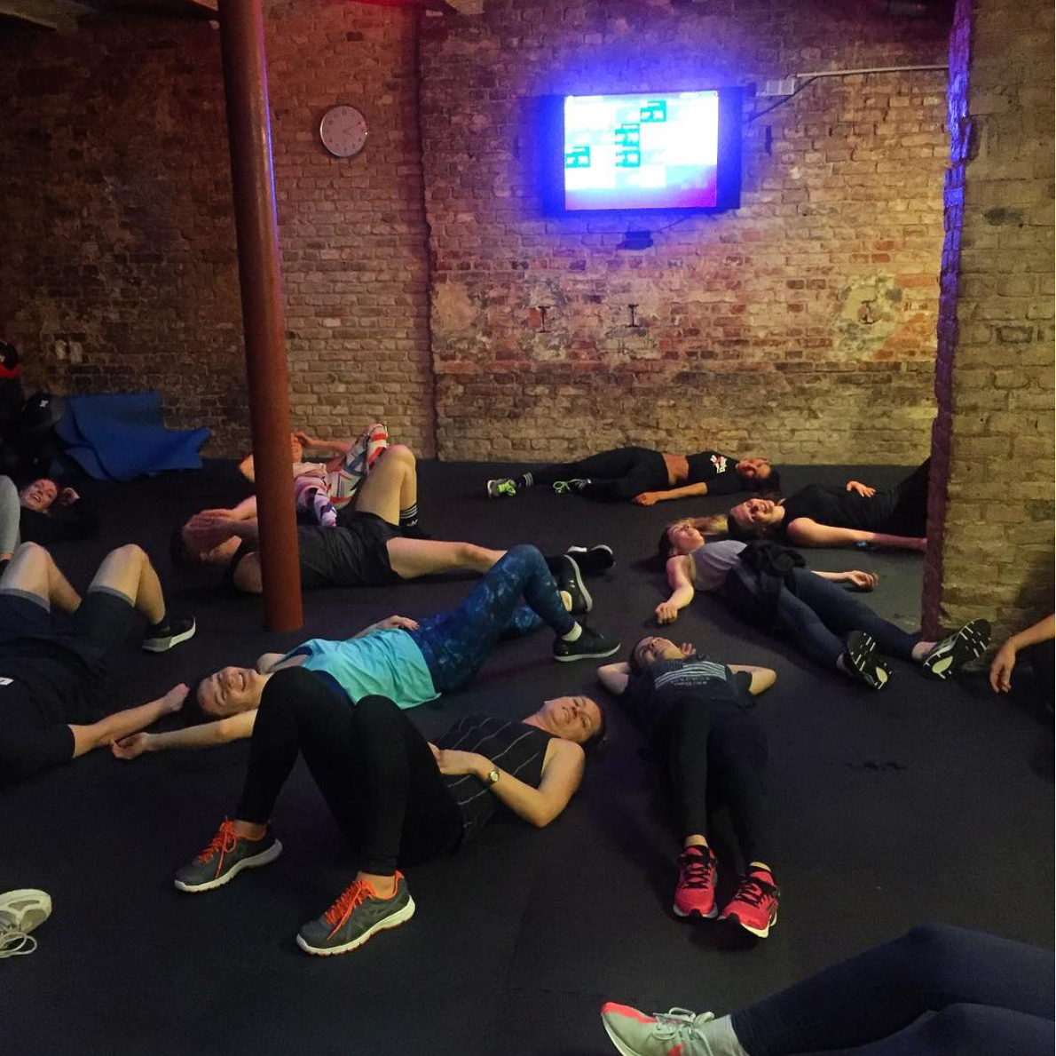 Girls and guys lying on the floor exhausted after a workout at Beat 81 Mitte location. Heart rates are visible on the monitor hanging on the brick wall