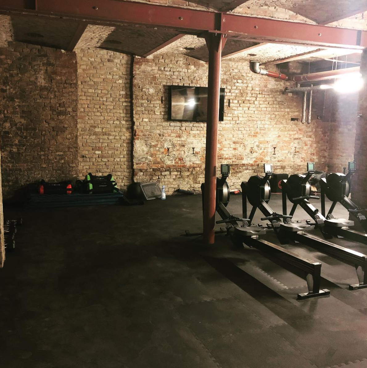 Beat 81 Mitte indoor location with a screen hanging on one of the brick walls and rowing machines and other workout gear standing in the room