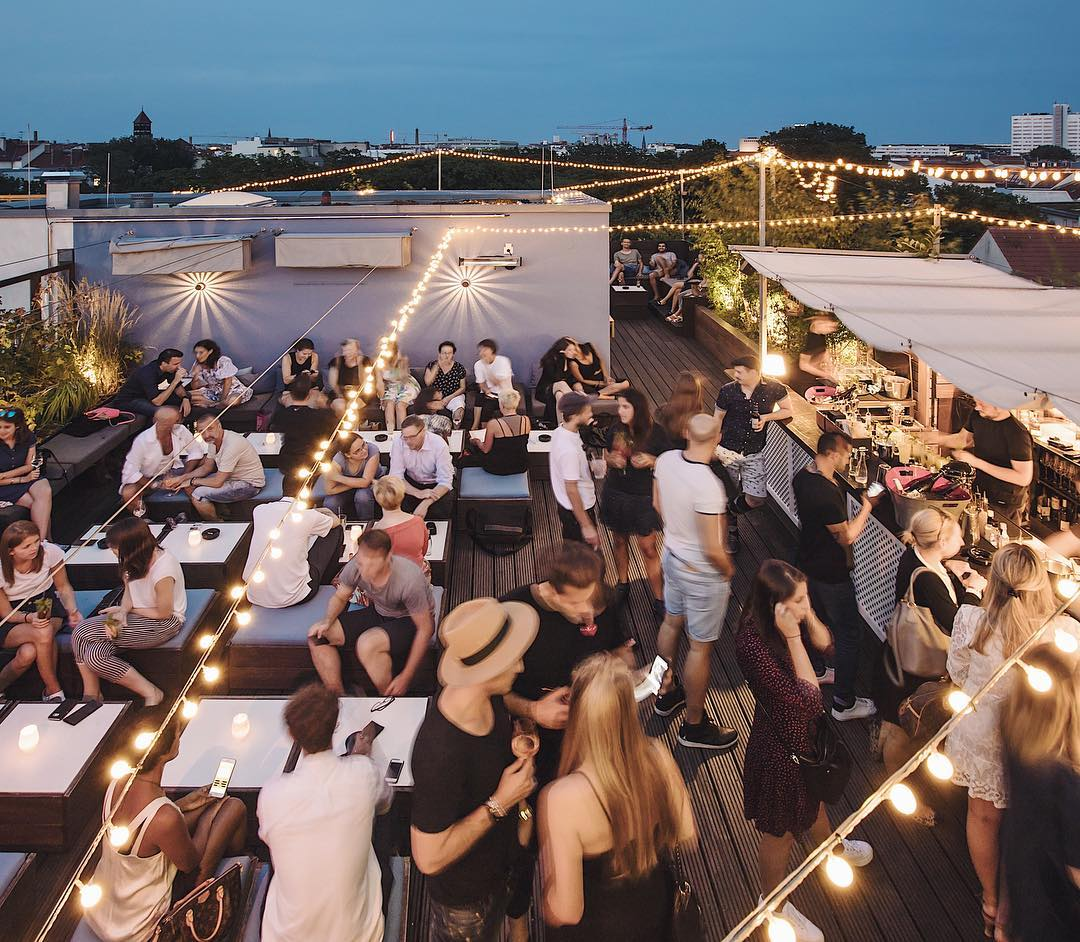 Summer night on Amano rooftop bar, people with drinks