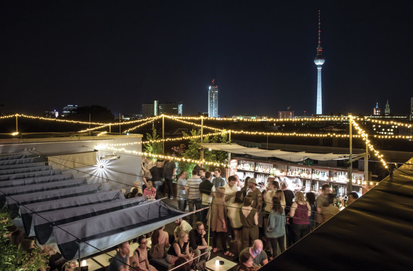Cool crowd having drinks on Amano Rooftop with view on tv tower