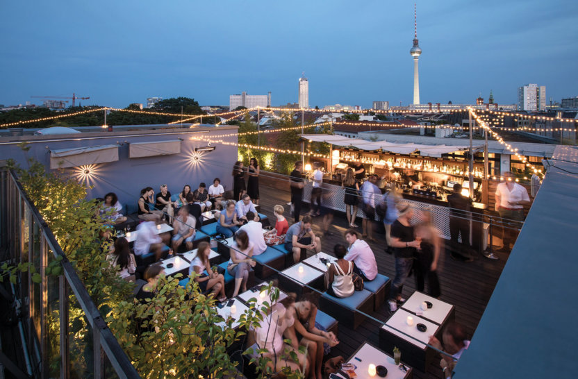 Young people on rooftop with drinks and view over Berlin