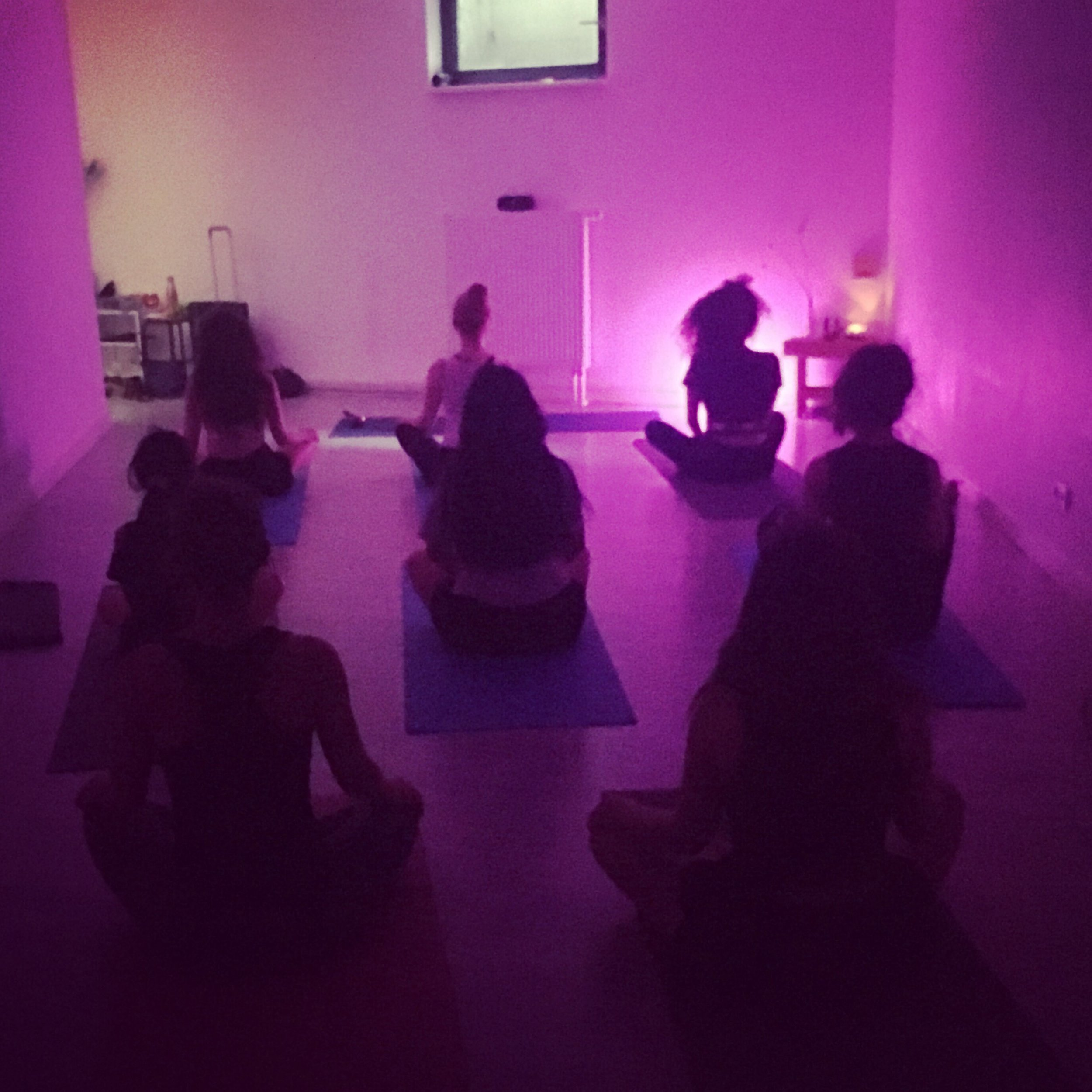 Yoga students in lotus pose on their mat in a dark room with purple light at Unknown Yoga Club Berlin with Rebecca Sunshine.
