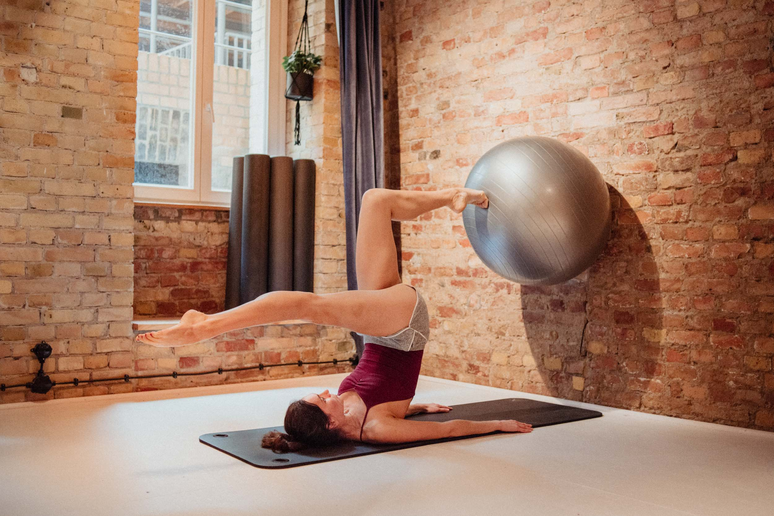 Daena from the Base Pilates Berlin doing a pilates move on a mat, pushing a gymnastic ball onto the wall with her foot.