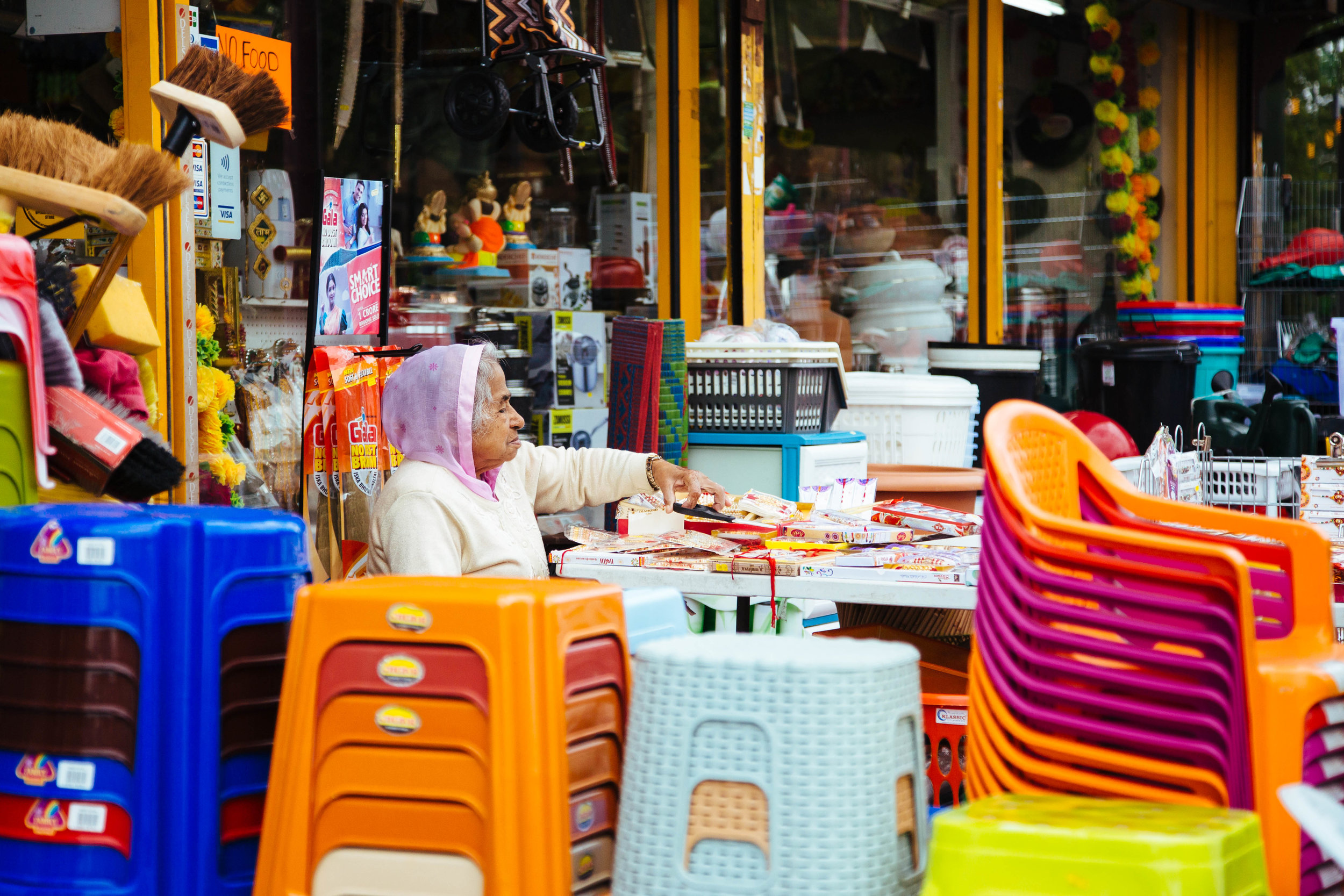 birmingham soho road market asian woman colourful plastic chairs