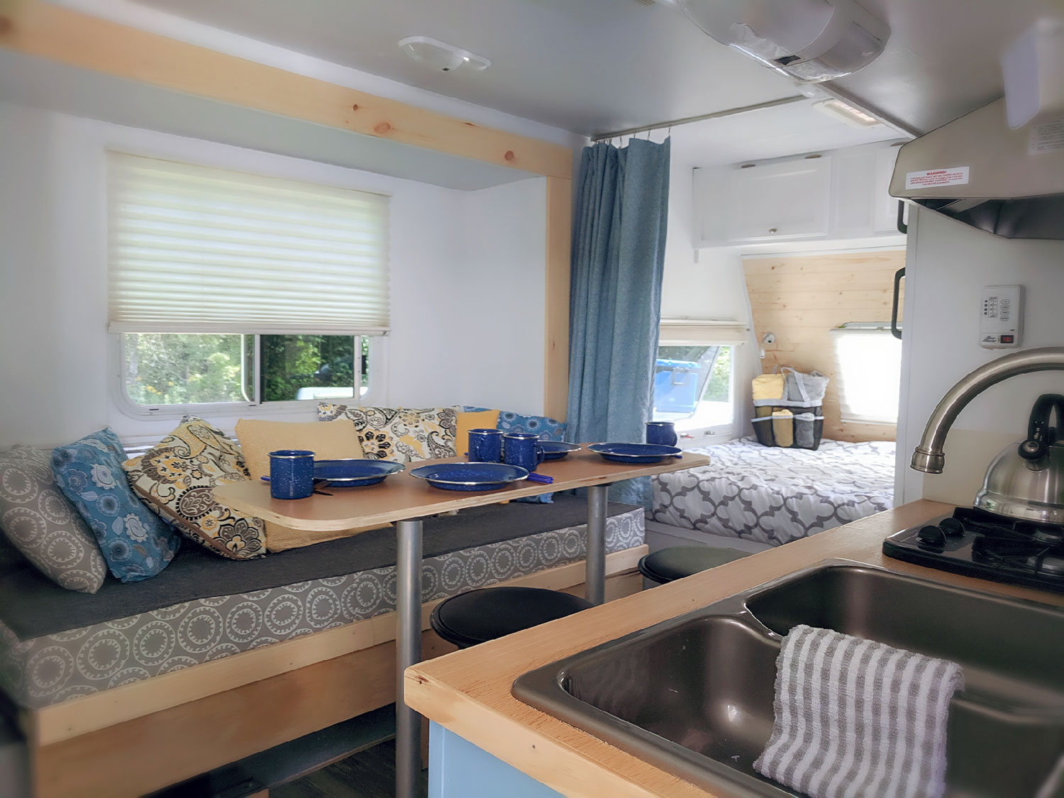 An interior shot of the Huxley, showcasing the dining area that converts into a bed measuring approximately 4½ feet x 6 feet, with a peek of the queen bunk and galley kitchen.