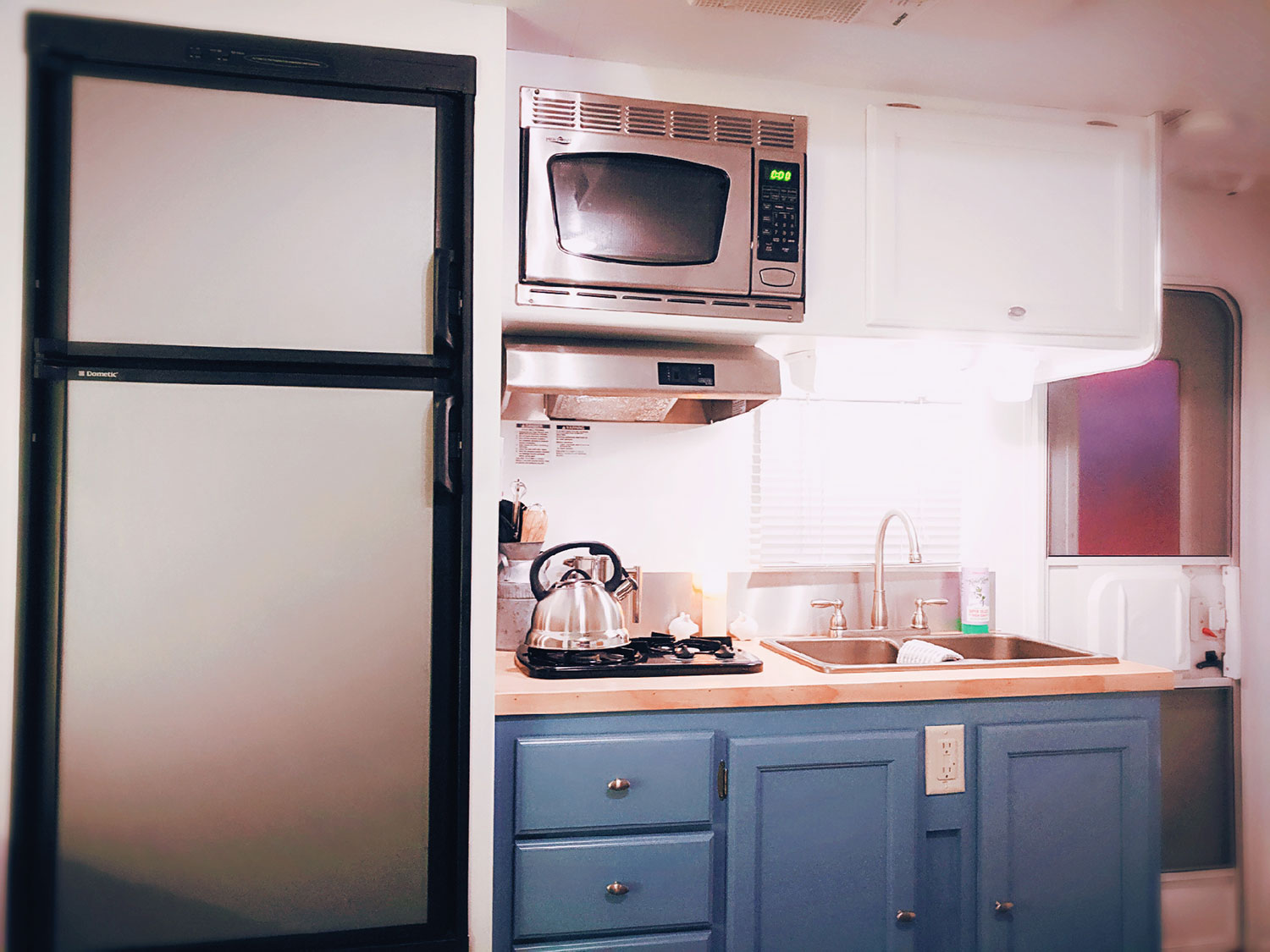 The galley kitchen includes a refrigerator and freezer, a microwave, a stove top with range hood, and a double sink.